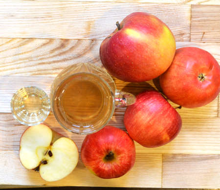 Apple cider vinegar in glass bottle and fresh apples on wooden background.