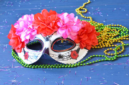 Dia de los muertos mask on a wooden background. Halloween carnival accessories. Day of the dead Masquerade holiday concept.