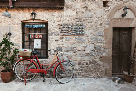 Vintage red bicycle in front of a stone building in Datca, Turkey