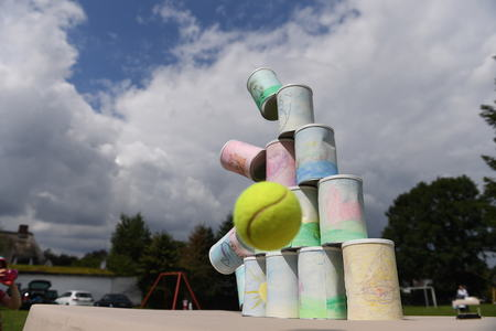 kids throeing a ball at cans