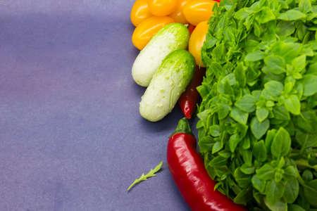 Healthy food Mini cucumbers, basil, Cherry tomatoes, chilli. blue background