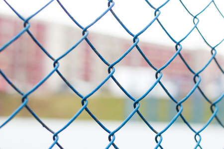 Fence on the sky, blue mesh fence, chain link fence, building back background. Soft focus.
