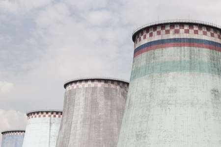 Multicolored cooling towers against a white-blue sky Stock Photo