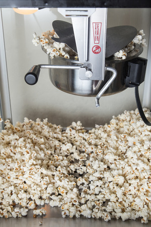 A popcorn machine in the middle of popping