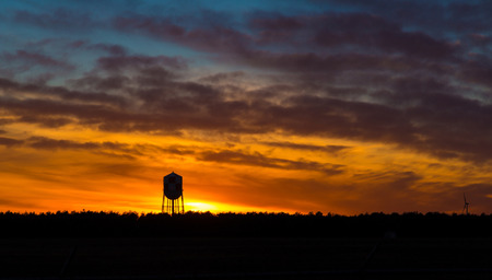 the water tower: A water tower is silhouetted against a colorful setting sun Stock Photo