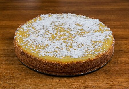 A whole cheesecake with powdered sugar resting on a table