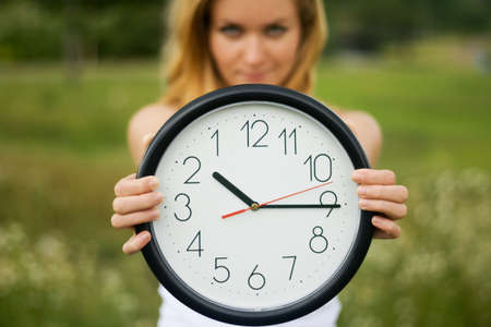 young woman with a wall clock Stock Photo
