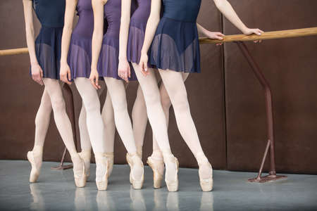 five ballet dancers in class near the handrail, legs only