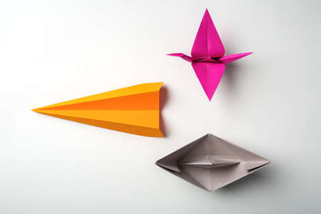 front photo of colored paper origami plane crane, boat photo
