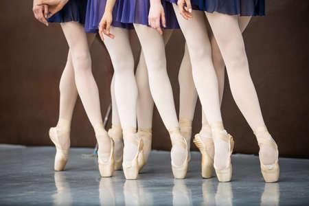 ballet clásico: Cinco bailarines de ballet en clase de baile cerca de la barra. Piernas solamente. El enfoque suave.