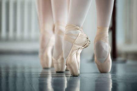 zapatillas ballet: Piernas bailarines en pointe blanco, cerca de la máquina de entrenamiento coreográfico. Bailarinas jóvenes.
