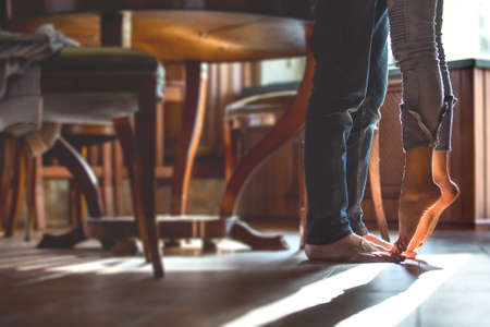 seduction: happy barefoot couple at the kitchen, girl standing on tiptoe try to kiss husband Stock Photo