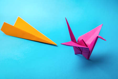 row of colored paper origami plane crane  on a blue background photo
