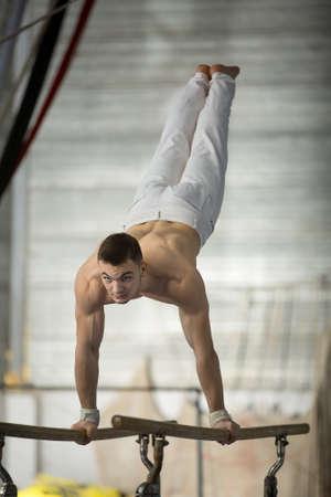 topless: Athl�te seins nus faire des exercices aux barres asym�triques dans le gymnase.