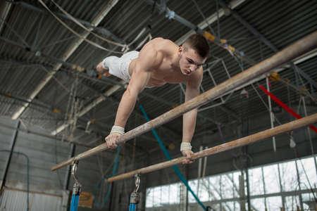 seins nus: Athl�te seins nus faire des exercices aux barres asym�triques dans le gymnase.