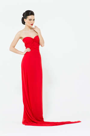 slinky: Sexy brunette in a slinky bright red evening dress isolated on white background in studio