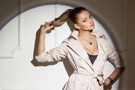 hair tied: Portrait of a stylish girl in the studio. Model is wearing a cloak. Beautiful hair tied in a ponytail.