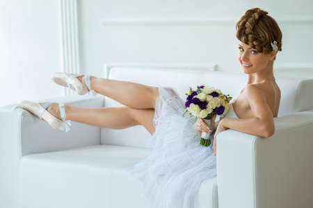 Ballerina with a beautiful bouquet sits on a snowy white sofa. Wearing pointe shoes on his feet. photo