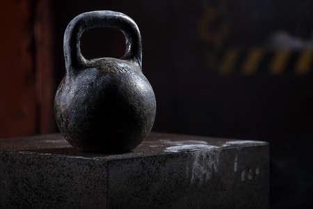 Zwarte oude sport gewicht staat op de kubus. Studio-opnamen in donkere kleuren.