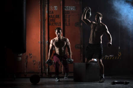 Two beautiful athlete train. One does kettlebell swings, squats with dumbbells other. The picture in the studio in a dark tone.