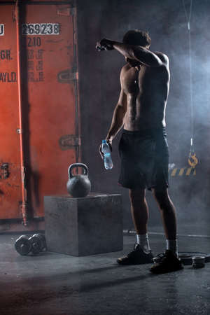 Tired athlete topless wipes the sweat from his forehead. In his hand a bottle of water. Studio shot in the dark tone.