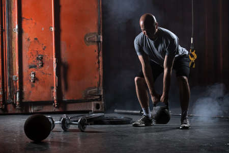 pesas: Atleta carismático calvo hacer sentadillas con pesas. Estudio de disparo en un tono oscuro. Foto de archivo