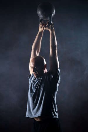 Bald charismatic athlete doing kettlebell swings. Studio shot in a dark tone. Stock Photo