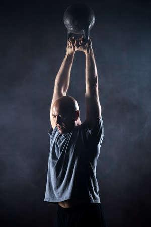 charismatic: Bald charismatic athlete doing kettlebell swings. Studio shot in a dark tone. Stock Photo