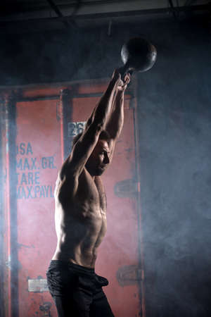 Beautiful athlete doing kettlebell swings. Profile picture. Athlete bare-chested. Studio shot in a dark tone.