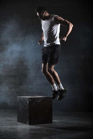 man jump: Athlete gave exercise. Jumping on the box. Phase touchdown. Studio shots in the dark tone.