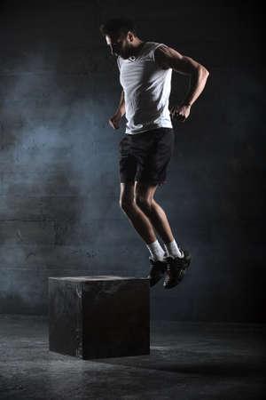 Atleta dio ejercicio. Saltando en la caja. Touchdown Fase. Fotografías de estudio en el tono oscuro. Foto de archivo