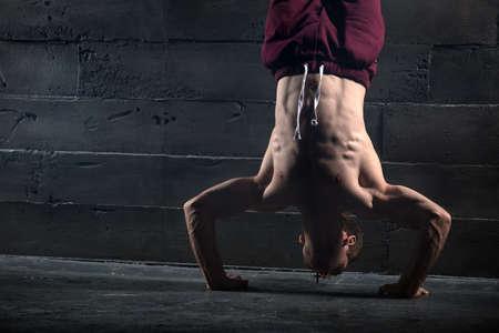 nackter junge: Athlet mit nackten Oberk�rper tun Push-ups auf seine H�nde, w�hrend er den Kopf in der N�he der Betonwand. Studio-Aufnahmen im Dunkeln Ton. Lizenzfreie Bilder