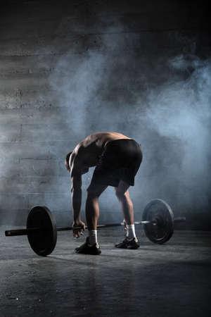 Portrait eines stattlichen Athlet von hinten. Athlete beugte sich zu der Bar und nahm ihre Hände hinter dem Nacken. Studio-Aufnahmen im Dunkeln Ton. Standard-Bild - 37458384