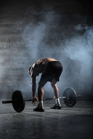 hand with dumbbells: Portrait of a handsome athlete from behind. Athlete leaned over to the bar and took her hands behind the neck. Studio shots in the dark tone. Stock Photo