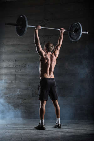 muscle building: Athlete performs a barbell exercise. Shot from behind.