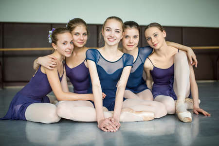 five young ballerinas sitting on the floor and looking to the camera with smiles