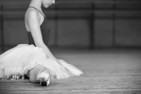 Young beautiful ballerina dressing on tutu stretches before practice. Zdjęcie Seryjne