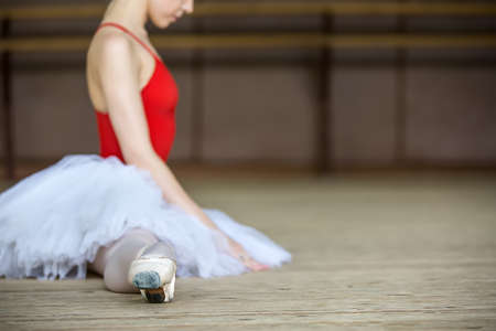 ballet bar: Young beautiful ballerina dressing on tutu stretches before practice. Stock Photo