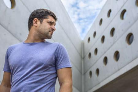 aside: handsome man standing on the background of a modern concrete building looks aside Stock Photo