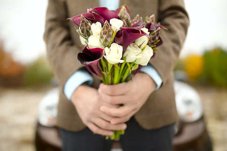 arm bouquet: The groom waits bride with a bouquet. Close-up of hand with a bouquet. Focus on the flowers. Stock Photo