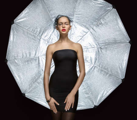 Attractive girl model with a veil on his face in black skin-tight dress on a background of silver umbrella. Umbrella - studio lighting element. photo