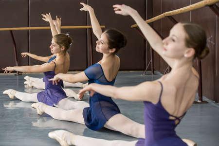 gymnastik: Junge Ballerinen auf den Unterricht der klassischen Choreographie sitzen in den Splits anmutig hob die H�nde bis in der N�he von Barre.