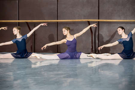 Young ballerinas on the lesson of classical choreography sitting in the splits gracefully raising his hands up near barre.
