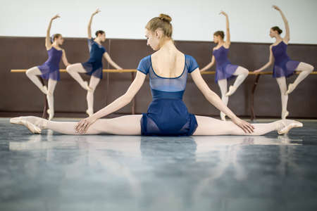 ballet: ballerina sitting on the floor with his back to the camera in the splits and dance class dancers practicing on the background