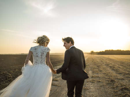 dynamic picture. newlywed couple running on the field holding hands at sunset.