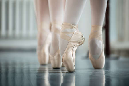 Legs dancers on white pointe, near the choreographic training machine. Young ballerinas.