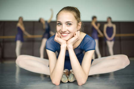 barre: Young ballerina sitting on the floor cross-legged and smiling. Against the background of four ballerina is doing exercises at the barre. Stock Photo