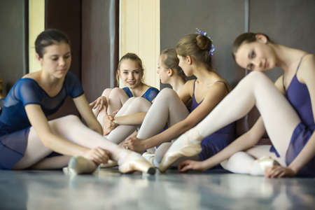 Five young dancers in the same dance costumes, resting sitting on the floor. Dance Class. Ballet School. Discussions yet with each other.