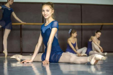 zapatillas ballet: Bailarina que se sienta en el suelo en las divisiones en unos bailarines de clase de baile que practican en el fondo. Bailarín está sonriendo.