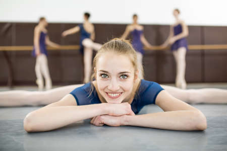 ballerina sitting on the floor with his face to the camera in the splits and dance class dancers practicing on the background